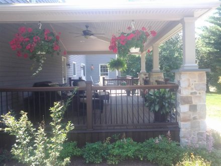 custom porch addition with stone columns and hanging planters