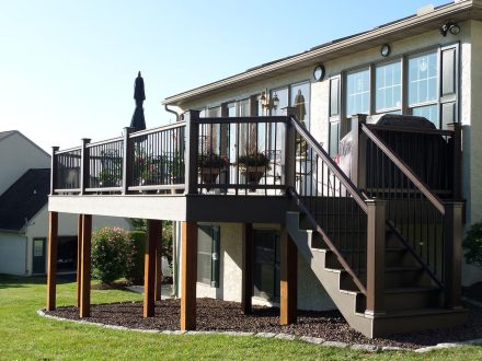 new brown composite deck addition with flower boxes and staircase