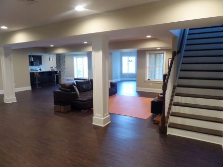 remodeled basement with columns, wood floors, and custom bar area